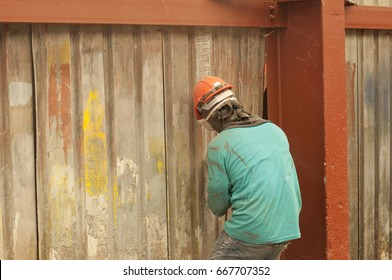 Back view of skilled worker in safety helmet grinding metal sheet in factory
