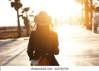 Back view of slender young woman wearing hat and coat walking down street on sunny spring day, heading to city beach to enjoy beautiful sunset. People, lifestyle, travel and vacations concept