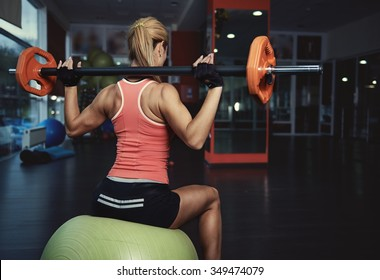 Back view of slim athletic woman with muscular body holding barbell exercising in gym. Concept of strength, health and endurance.