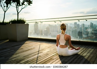 Back view of slim female in active wear sitting in lotus pose recreating on spiritual practice and keeping healthy lifestyle, caucasian female relaxing on yoga practice feeling calm on rooftop terrace