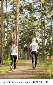 Back view of slim runners jogging in the park