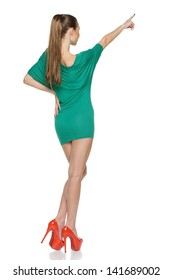 Back view of slim young female wearing green mini dress in full length pointing up, against white background