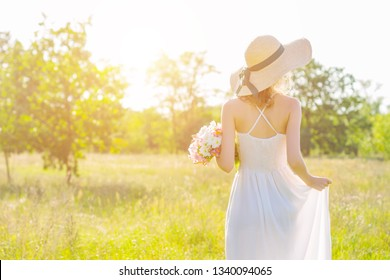 Back view of slim young woman in fashionable hat holding bouquet of pink and white flowers. Romantic girl in white dress is walking and dreaming on spacious field at sunset. Provence style.