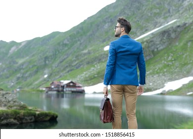 back view of smart casual man wearing blue coat, holding suit case and looking to side, admiring nature, outdoor at Balea Lake, Romania