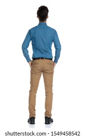 back view of smart casual man in blue shirt looking up and holding hands in pockets, standing isolated on white background, full body