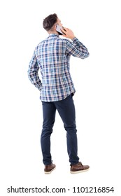 Back view of smart casual young man talking on the cell phone and looking up. Full body isolated on white background.