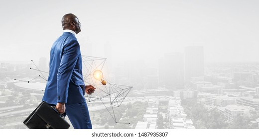 Back view of smiling black businessman with a briefcase on a cityscape background with 3d graph and a burning lamp
