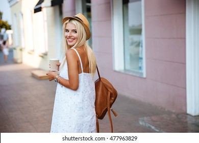 Back view of smiling cheerful blonde girl in white dress holding take away cup outdoors
