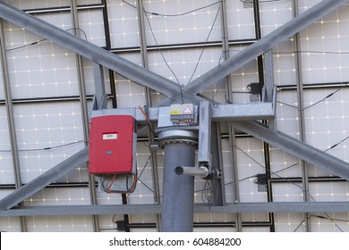 Back view of solar panel: turning gear for tracking the sun and correct orientation and red inverter to transform direct current into alternate