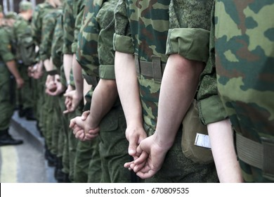 Back view. Soldiers in camouflage uniforms stand on the manifestation, hands behind their backs.