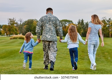 Zurück Blick Soldaten Familie laufen. Soldat im Urlaub. Vier Familienmitglieder gehen zusammen und halten Händchen.