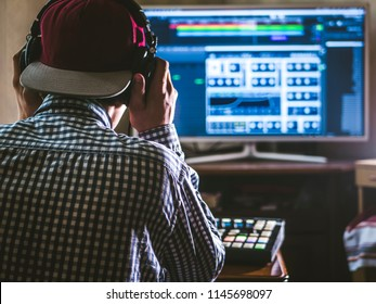 back view of sound engineer in snapback and holding headphones on head monitoring music in studio
