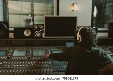 back view of sound producer working at studio while recording song