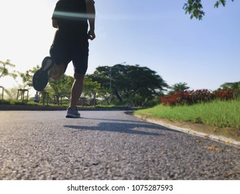 Back view of sport runner man running on the road against the blue sky background in sunny day. Outdoor Running in the public park.