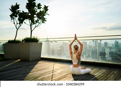 Back view of sports woman feeling inspiration during yoga training on rooftop terrace in megalopolis, slim girl in active wear meditating in pose keeping perfect body shape and healthy lifestyle