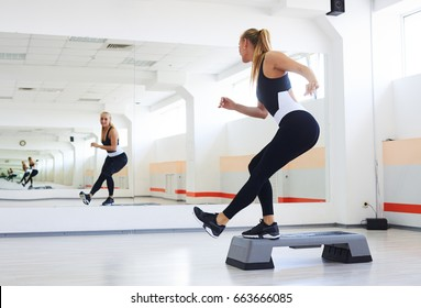 Back view of sporty athlete having a step aerobics in a gym. Woman doing c�orner knee step
