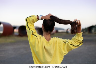 Back view of sporty girl getting ready for running workout. Young female athlete training outdoor on urban industrial zone.