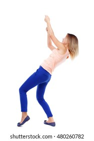 back view of standing girl pulling a rope from the top or cling to something. Isolated over white background. The blonde in a pink shirt pulling the rope from above.
