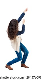back view of standing woman pulling a rope from the top or cling to something.  Rear view people collection.   Isolated over white background. Girl in sheepskin jerkin pulling a rope from the top.