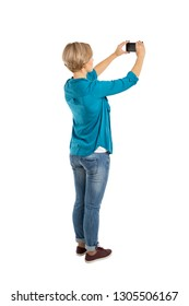Back view of standing young beautiful woman and using a mobile phone isolated on white background