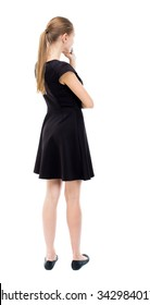 back view of standing young beautiful  woman.  girl  watching. Rear view people collection.  backside view of person.  The blonde in a black dress thoughtfully put a hand to his chin.