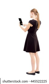 back view of standing young beautiful  girl with tablet computer in the hands of. girl  watching. Rear view people collection. The blonde in a black short dress working on the tablet.