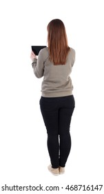 back view of standing young beautiful  woman  using a mobile phone. girl  watching. Rear view people collection.  backside view of person.  Isolated over white background. A girl in a gray jacket's