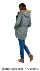 back view of standing young beautiful  brunette woman in park. girl in warm jacket  watching. Rear view people collection.  backside view of person.  Isolated over white background.