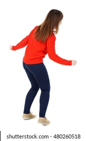 back view of standing young beautiful woman in jeans. Isolated over white background. Girl in a red jacket dancing.