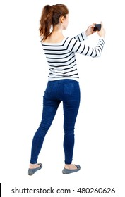back view of standing young beautiful woman using a mobile phone. girl watching. Rear view people collection. Girl in a striped sweater photographs mobile phone.