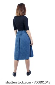 back view of standing young beautiful  woman.  girl  watching. Rear view people collection.  backside view of person. A girl in a blue checkered skirt shows her hand to the left.