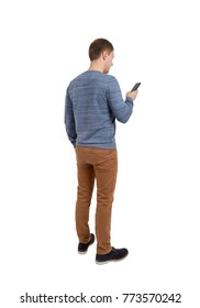 Back view of standing young men and using a mobile phone. Isolated on white background.