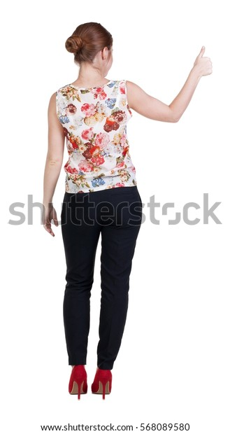 back view of standing young redhead business woman showing thumb up. beautiful businesswoman in black suit gesturing ok sign. Rear view people collection.