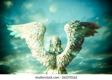 back view of the statue of an angel composite with mystical sky