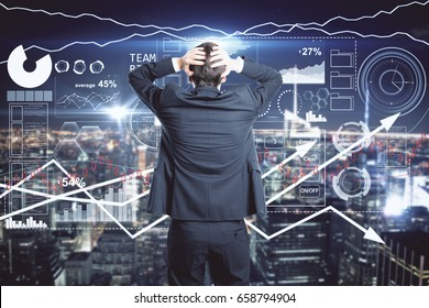 Back view of stressed young businessman looking at night city with forex chart. Crisis concept