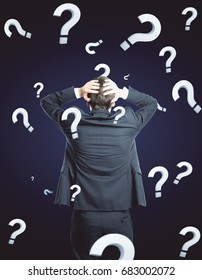 Back view of stressed young businessman on dark background with question marks. Confusion concept