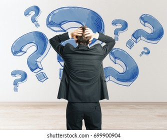Back view of stressed young businessman looking at concrete wall with drawn question marks in interior. Stress concept
