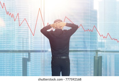 Back view of stressed young businessman looking at virtual screen with forex charting in front of windows office overlooking the city at sunrise .