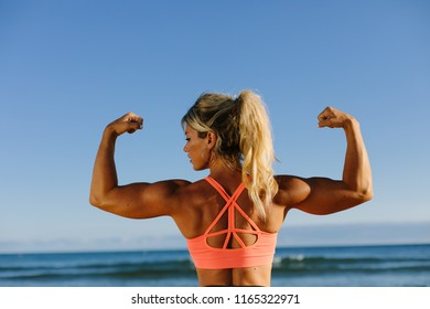Back view of strong fitness woman showing her arms biceps at the bech.