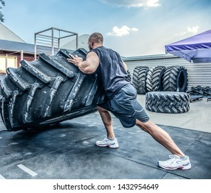 back view of strong muscular fitness man moving large tire in street gym. Concept lifting, workout training.