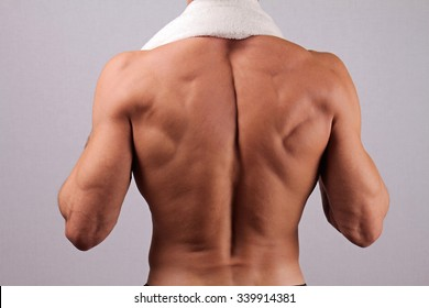 Back view of strong muscular male body, closeup of fitness man with a white towel slung around his neck. bodybuilding, work out, sport, hard work, motivation, active lifestyle concept