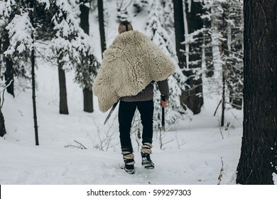 back view strong viking warrior with mohawk haircut and wolf pelt armor holding axe and walking in winter woods before historical battle, scandinavian traditional clothing for lumberjack