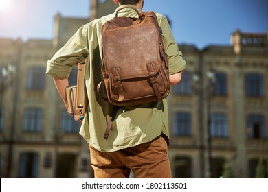 Back view of a student with a leather backpack over his shoulder carrying his textbooks