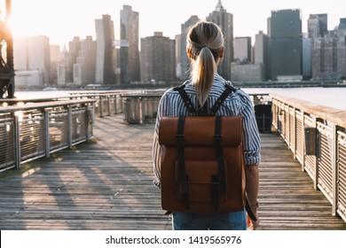 Back view of stylish female tourist with traveling backpack standing on American urban setting and examanise landmark of Manhattan district, millennial woman exploring United States during journey