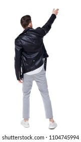 Back view of a stylish man in a leather jacket points his hand upwards. Rear view people collection.  backside view of person.   A stylish businessman in a leather jacket raised his hand