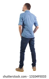 Back view of a stylish man. Rear view people collection.  backside view of person.  Isolated over white background. A man in a shirt is looking sideways with his hands in his jeans pockets.