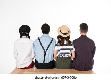 Back view of stylish young friends sitting together on wooden bench isolated on white