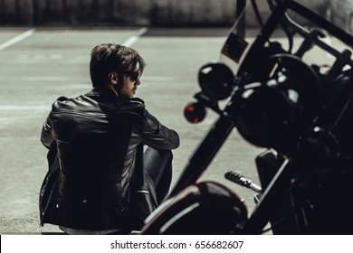 Back view of stylish young man in leather jacket sitting near motorbike and looking away