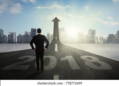 Back view of successful businessman standing and looking at upward arrow on the end of road
