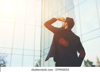 Back view of successful man entrepreneur looking up on modern skyscraper while standing outdoors, young executive male director admires something on the distance during work break outside of company